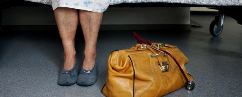 Oudere dame in ziekenhuisbed met dokterstas.